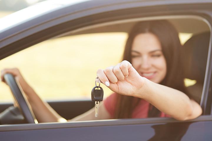 Jovem mulher sorrindo sentada em carro com mão ao volante e braço para fora da janela mostrando chave do veículo