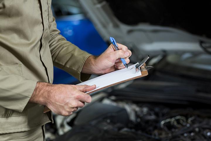 Mãos de homem segurando prancheta e preenchendo papel durante perícia de veículo para laudo cautelar