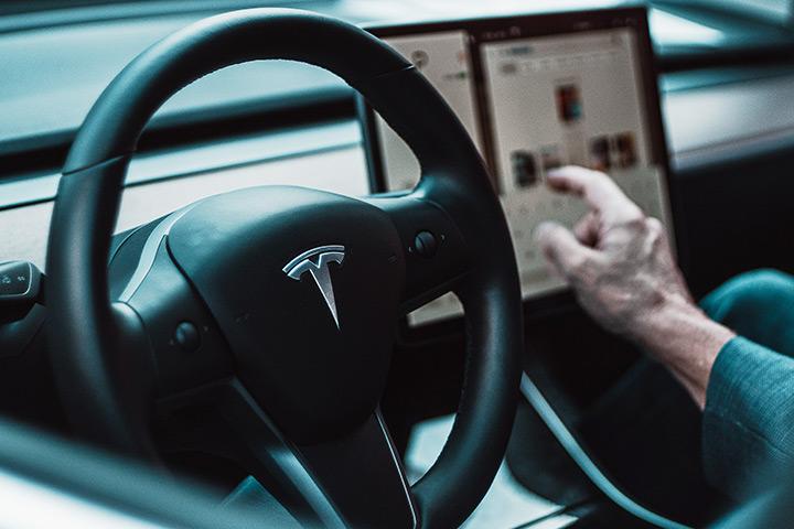 Interior de carro Tesla com volante em destaque e central multimídia ao fundo com motorista operando sistema