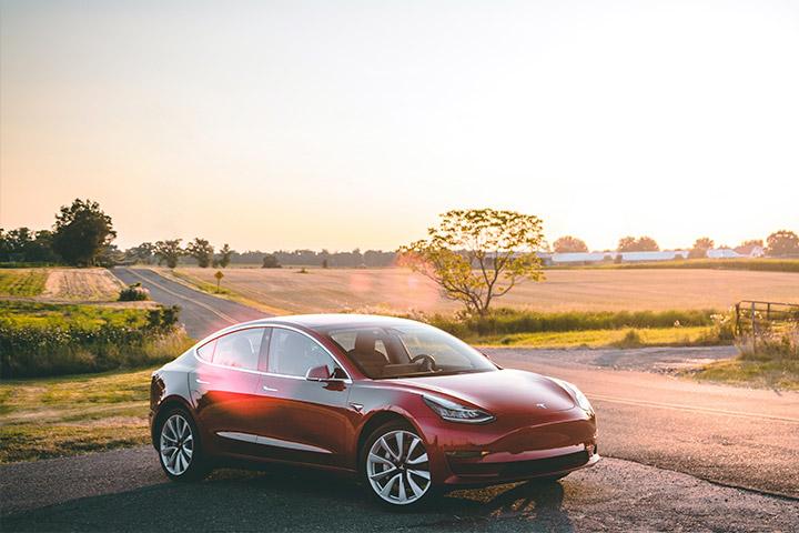 Tesla Model 3 estacionado em acostamento de estrada rural com luz do sol da tarde iluminando sua pintura