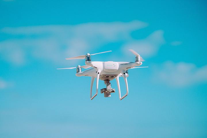 Drone branco com quatro hélices voando com céu azul ao fundo