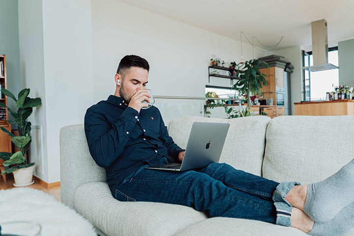 Jovem rapaz relaxando em sofá de sua casa e acessando site da Carupi para comprar e vender carros online