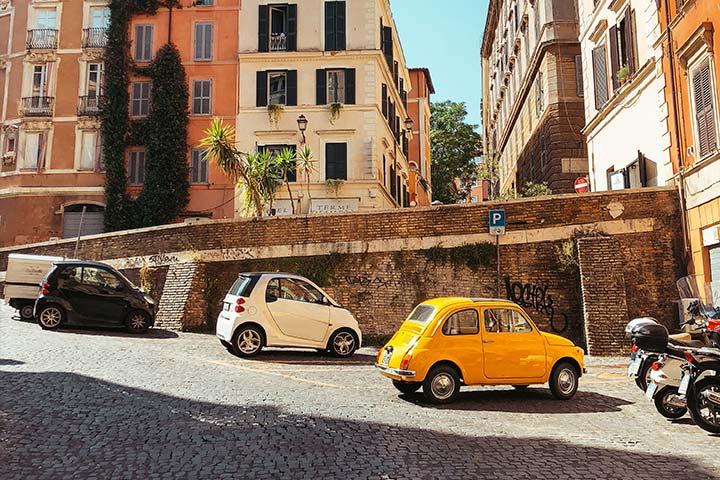 Cidade italiana com carros pequenos estacionados na rua