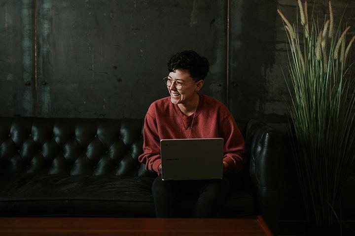 Jovem mulher sentada em sofá de couro vintage de estilo inglês acessando Carupi em seu notebook