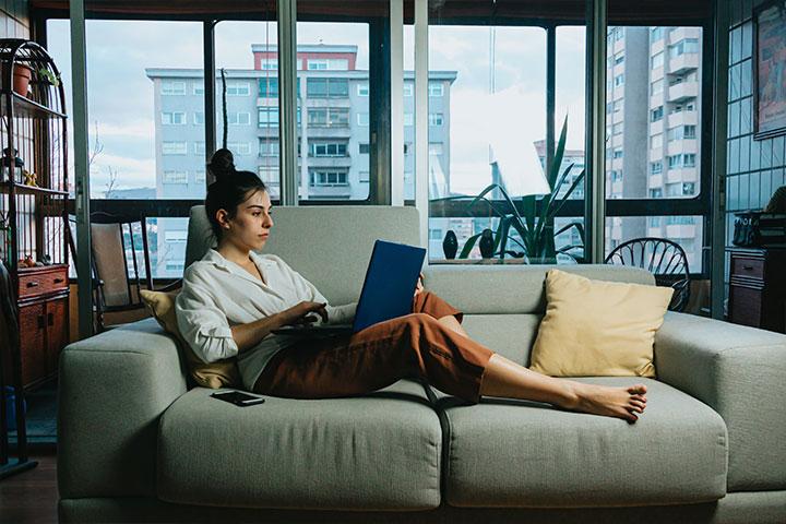Jovem mulher relaxando no sofá de sua casa e acessando plataforma da Carupi em seu notebook