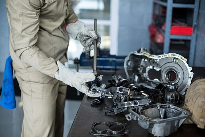 Mecânico desmontando peças de motor em bancada de oficina para  efetuar retífica do virabrequim