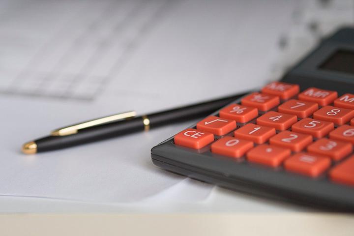 Close em calculadora com teclas alaranjadas sobre papéis e com caneta ao lado