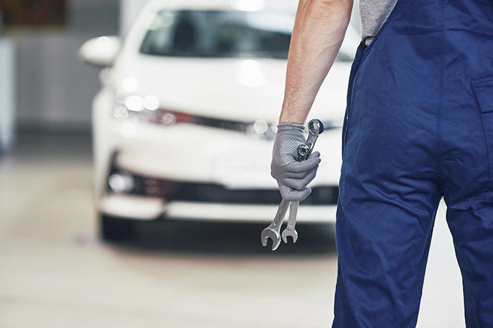 Mecânico de costas segurando ferramentas olhando para carro branco em sua oficina