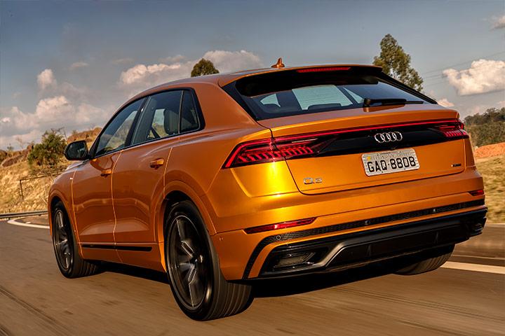 Audi Q8 de cor laranja visto por trás em rodovia com paisagem ao fundo