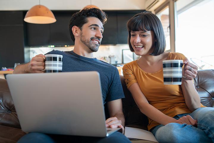 Jovem casal relaxando em sofá de casa e acessando website da Carupi para comprar carros usados online