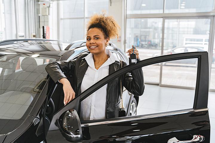 Jovem mulher afro-americana sorrindo ao segurar a chave de seu carro novo em concessionária de veículos