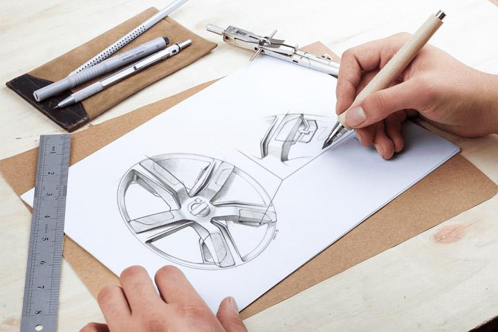Close em mãos de projetista de carros desenhando esboço de roda em papel usando lápis e régua
