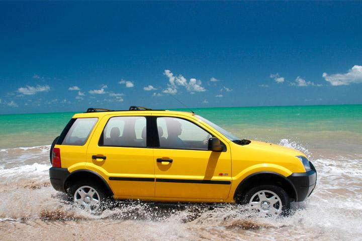Ford Ecosport em cor amarela acelerando à beira-mar em cenário de praia