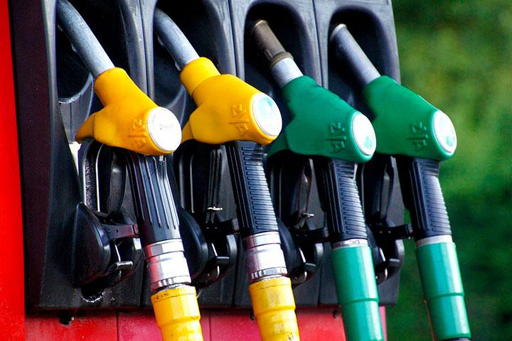 Bomba de combustível em posto de gasolina com destaque para mangueiras em cores amarela e verde