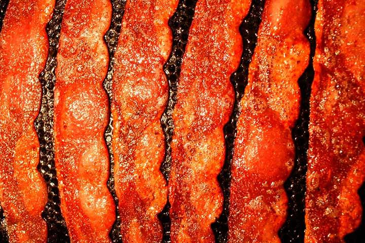 Fatias de bacon em fritura com borbulhas de óleo na chapa