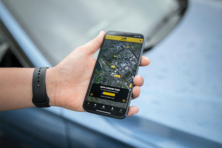 Close em mão de rapaz segurando smartphone com aplicativo de rastreamento veicular aberto mostrando mapa e posição de veículo