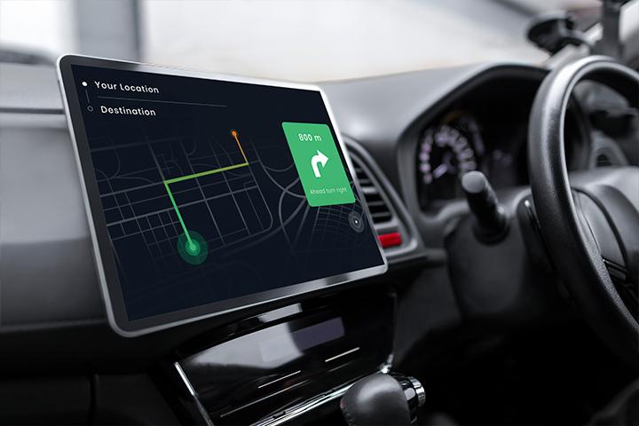 Console de carro mostrando volante e tela multimídia indicando mapa e rota de veículo
