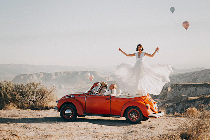 Fusca vermelho conversível parado à beira de um desfiladeiro em cenário desértico com noiva em pé no banco de trás e vestido esvoaçante