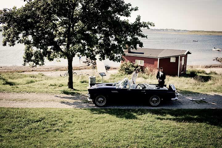 Carro para casamento parado em frente a casebre com noivos dentro e grande lagoa ao fundo