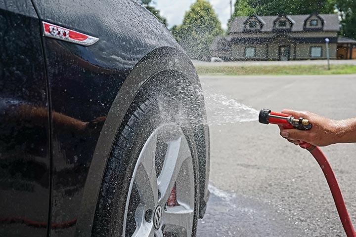 Lateral dianteira de carro da Volkswagen recebendo esguicho de mangueira durante lavagem de carro