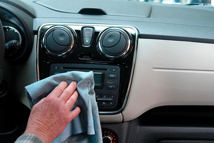 Console de carro sendo limpo por homem com flanela