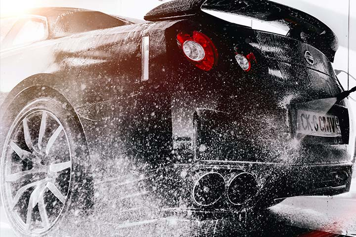 Traseira de carro esportivo da Nissan sendo esguichada para limpar sabão durante lavagem automotiva
