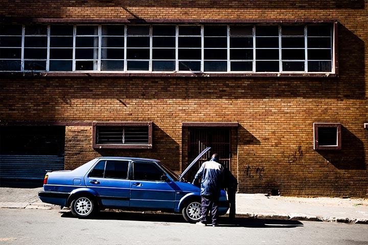 Carro antigo azul com problemas mecânicos estacionado em rua e sendo avaliado por profissionais