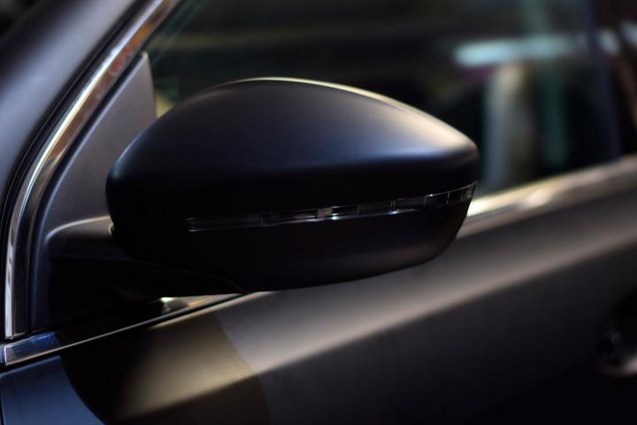 Detalhe de espelho retrovisor de carro com envelopamento automotivo preto fosco