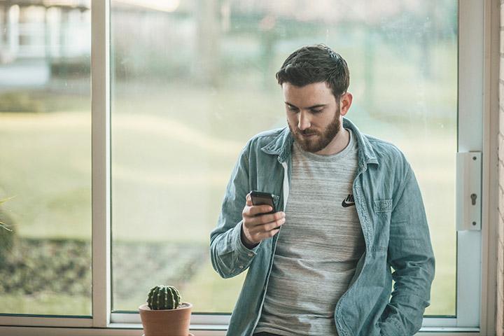 Jovem rapaz em frente a janela de sua casa vendendo seu carro pelo celular usando app da Carupi