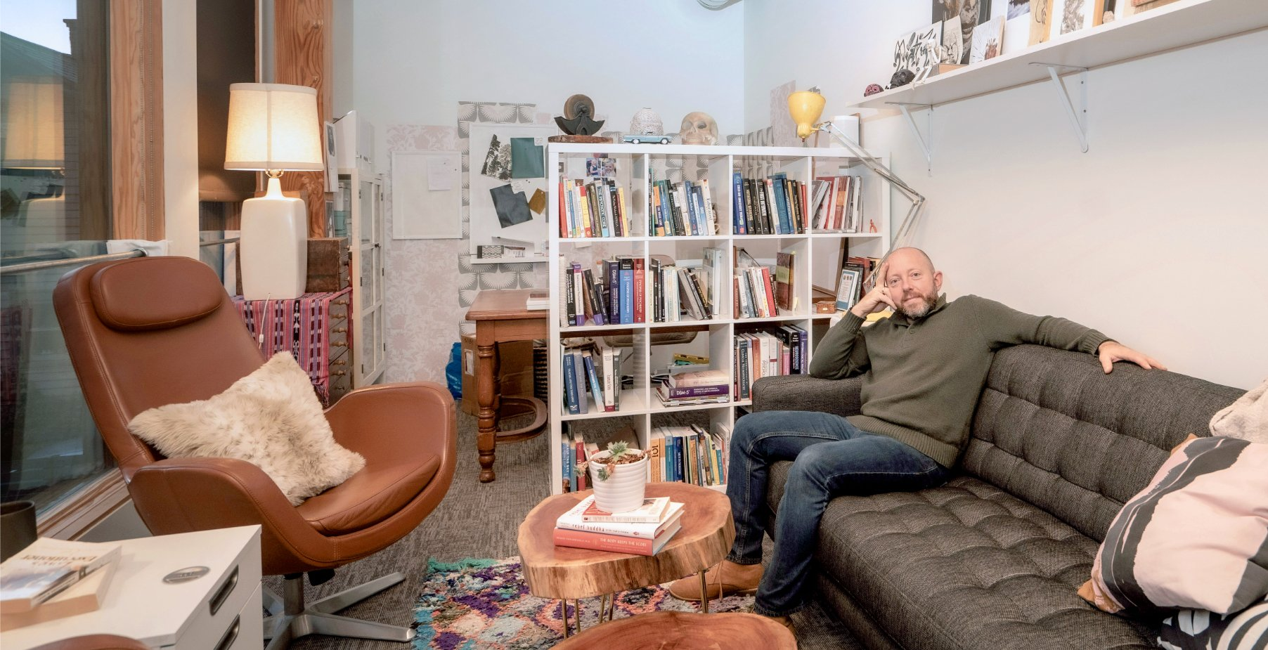 A landscape photo of Dr.Jake in his office. He sits patiently on a comfortable couch. A large shelf stands prominently out from the wall, each cubby host of a variety of books, thick and thin. Oddities and curiosities lay about the room on shelves and tables. The overall atmosphere of this space is friendly, relaxed, and a bit quirky.