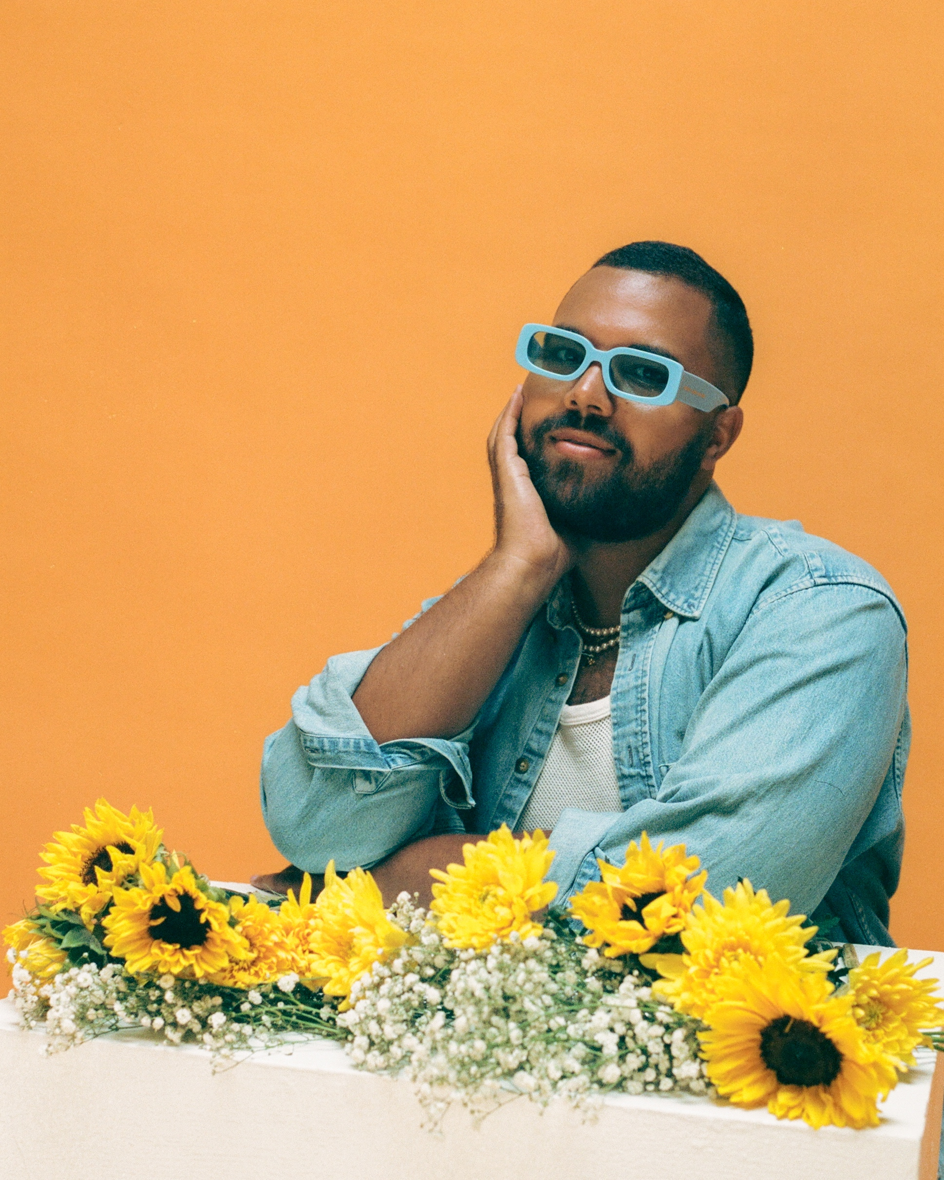 A portrait of Micah wearing sunglasses and holding sunflowers