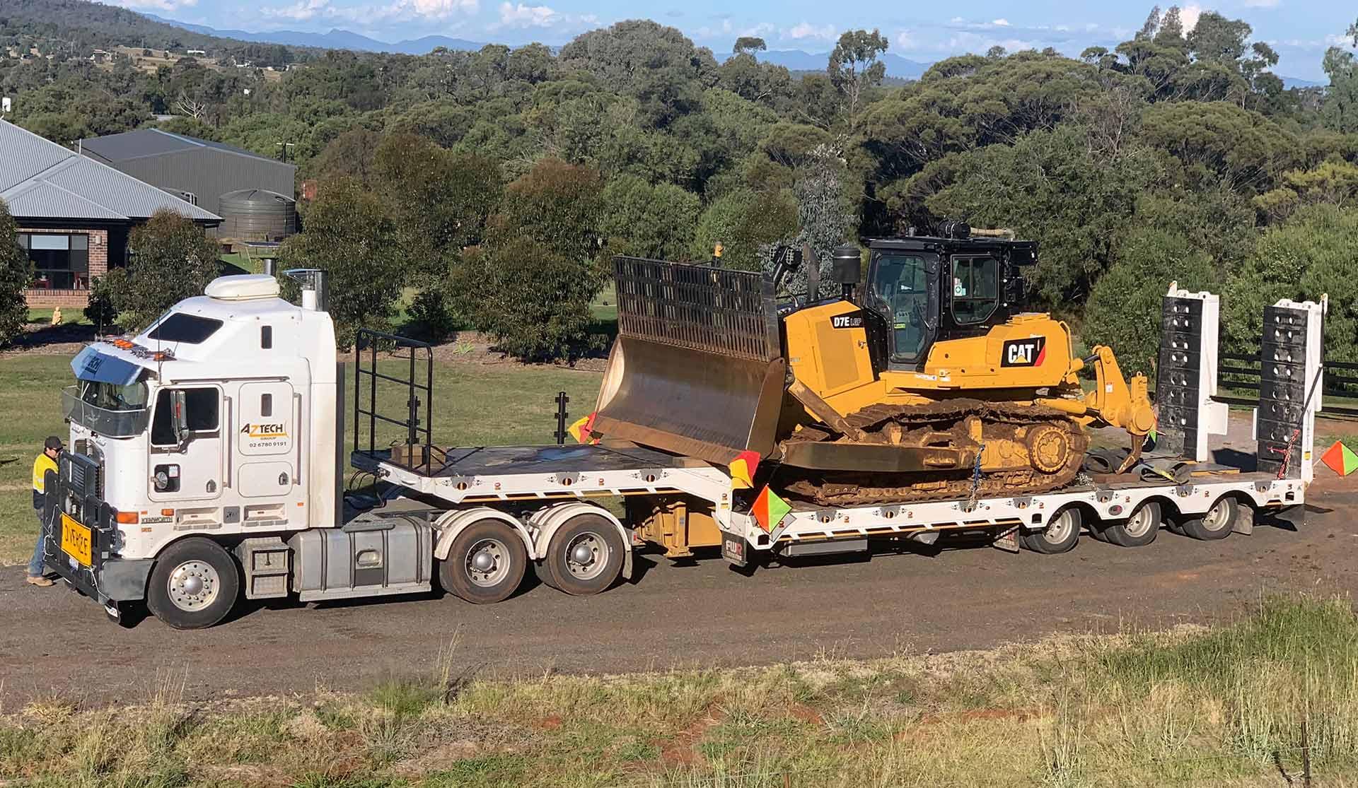Aztech 24 wheeler truck carrying a CAT D7 tractor