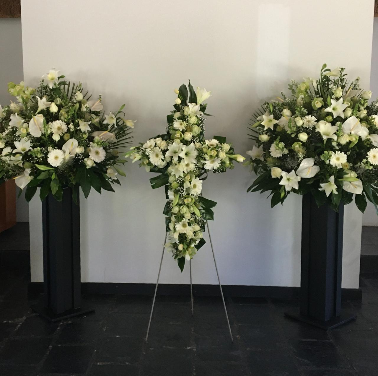 White flowers in the shape of a cross with matching arrangements. Please call for a quote.