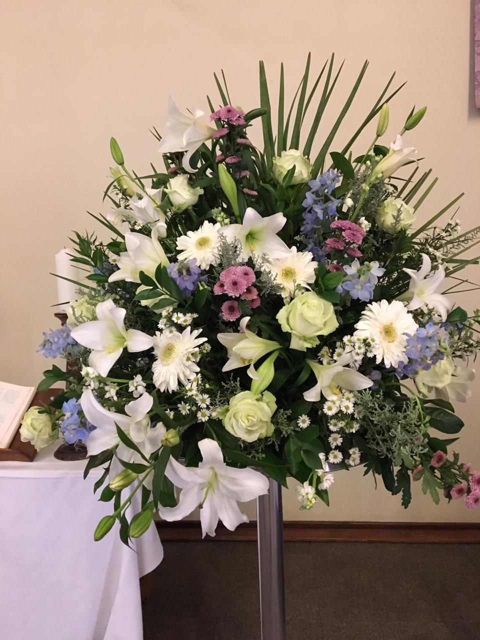 Church arrangement with white pinks and purple colored flowers