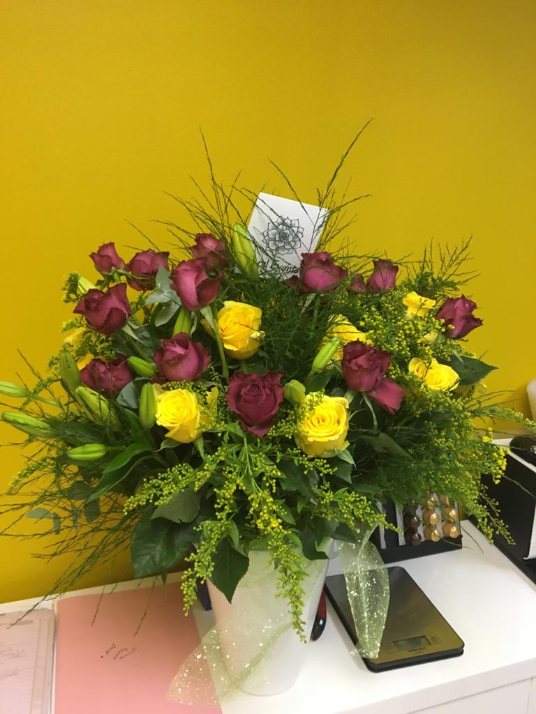 Purple and yellow flowered roses in a vase from