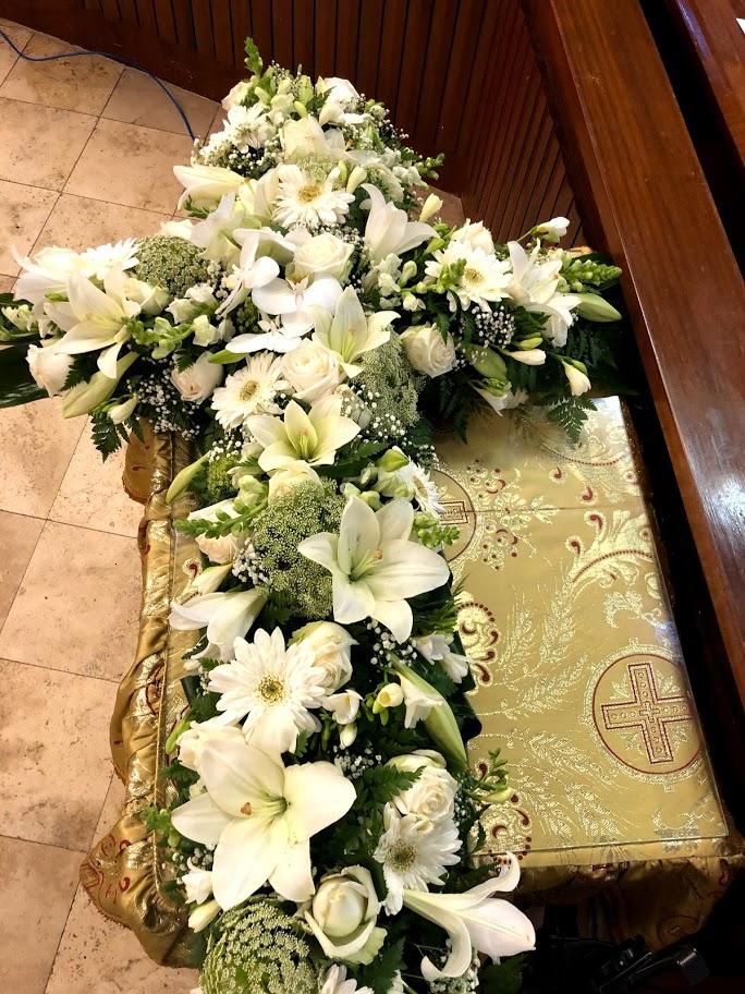 Cross with white seasonal flowers