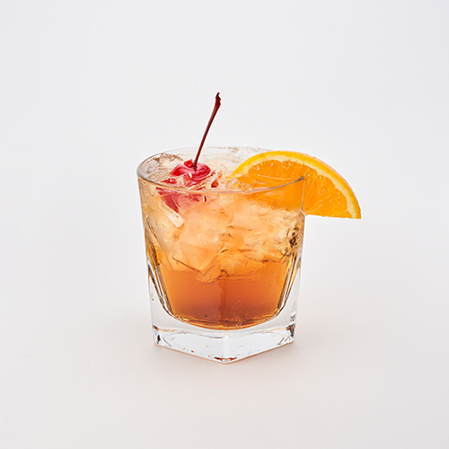 Jack Daniels Whiskey, Amaretto & Coca Cola garnished with an orange slice and a cherry