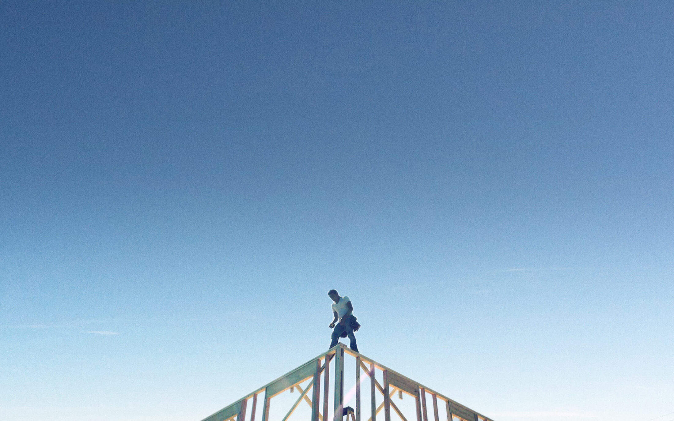 Man standing on top of a house's framework.