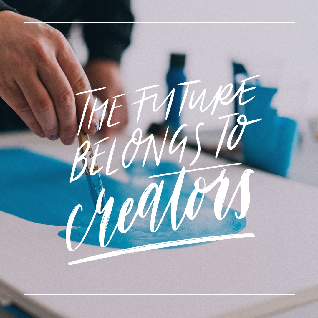 """Artist painting with """"The Future Belongs to Creators"""" written on top"""