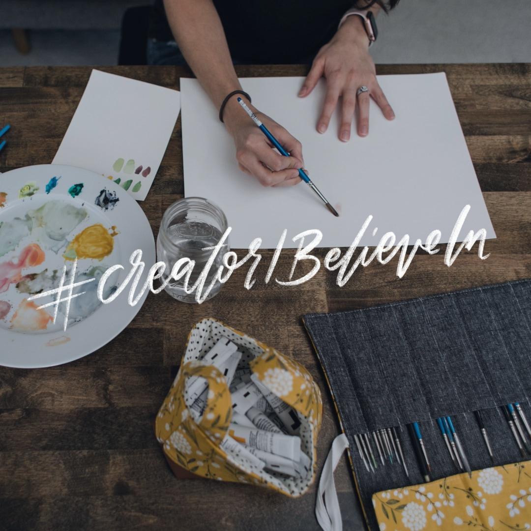 Artist painting on a table with #CreatorIBelieveIn written on top