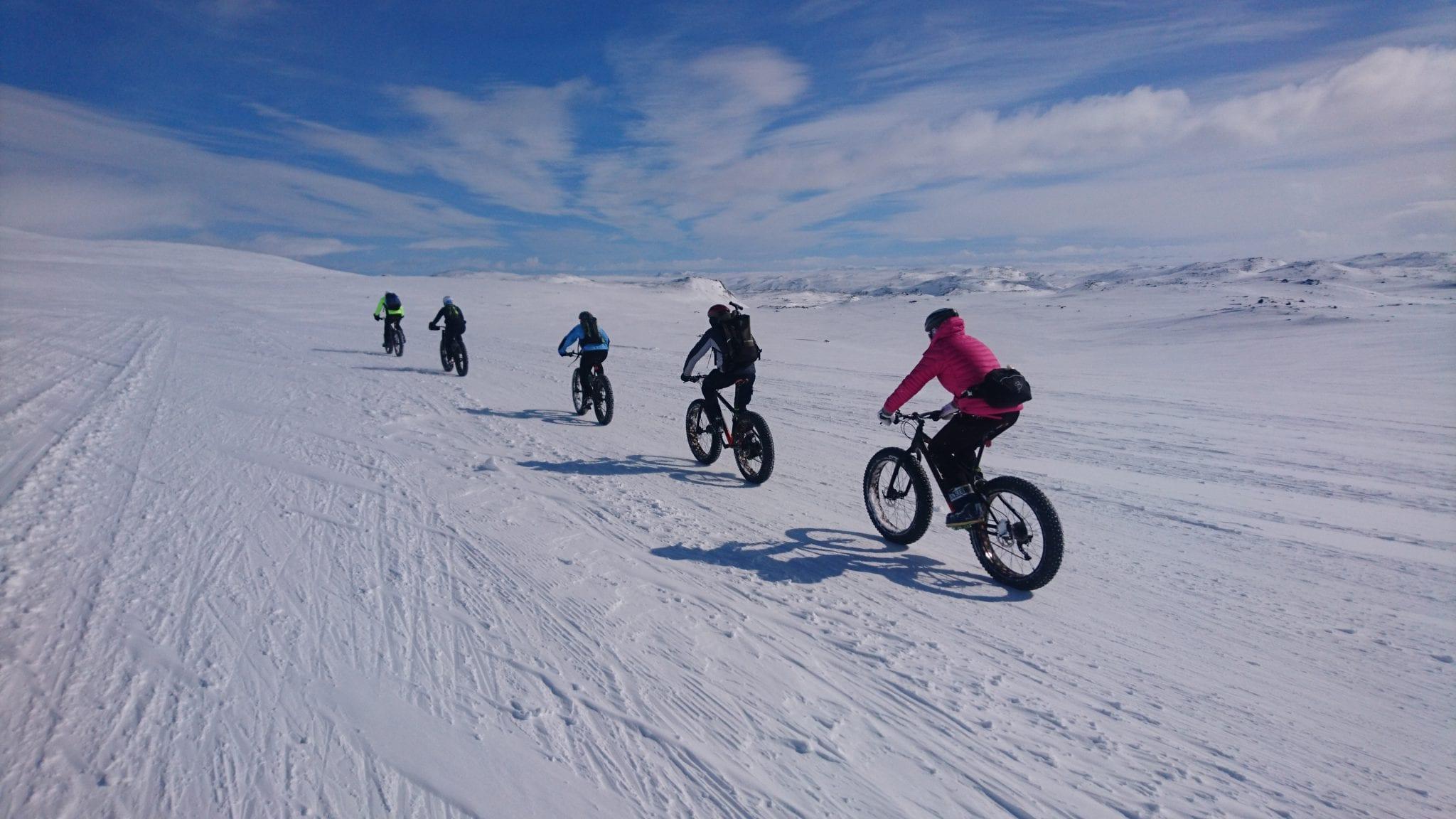Mrennesker på FatBike gjennom snødekket landskap