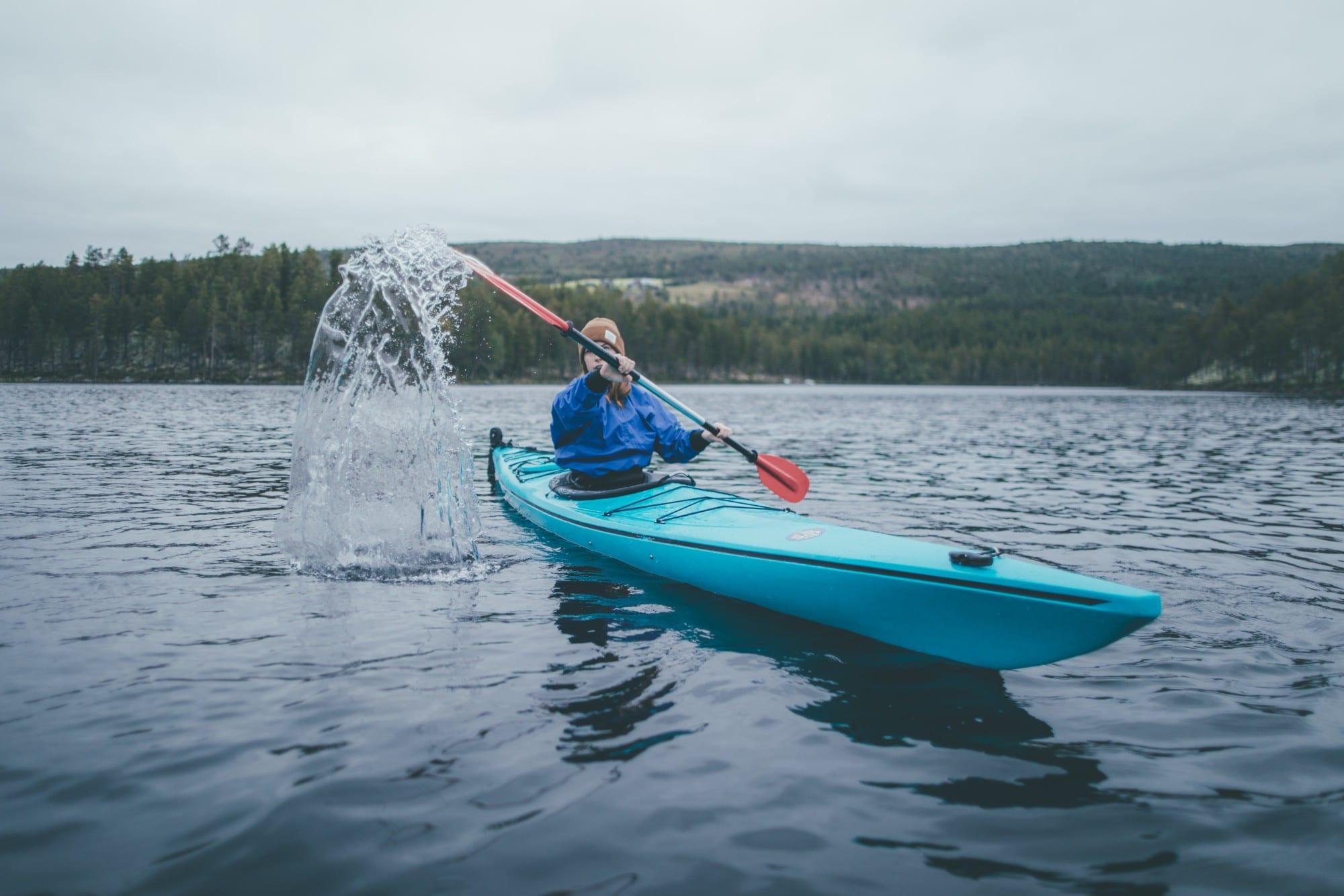 En person som er ute og padler kajakk. Åren spruter vann.