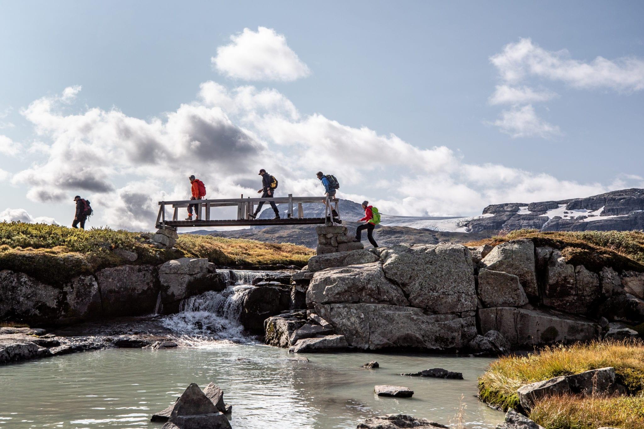 Fire personer som går over en gammel trebru. En liten elv renner foran, mens det er fjell i bakgrunnen.