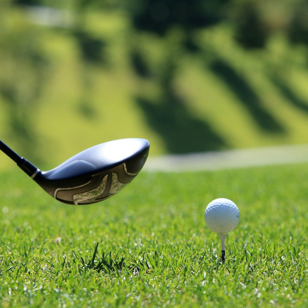 Golfkølle og ball på gress