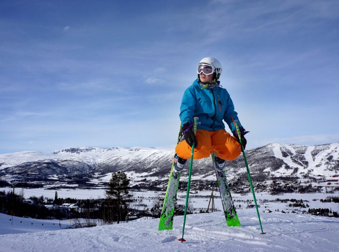 Alpinist som står på tuppene av skiene