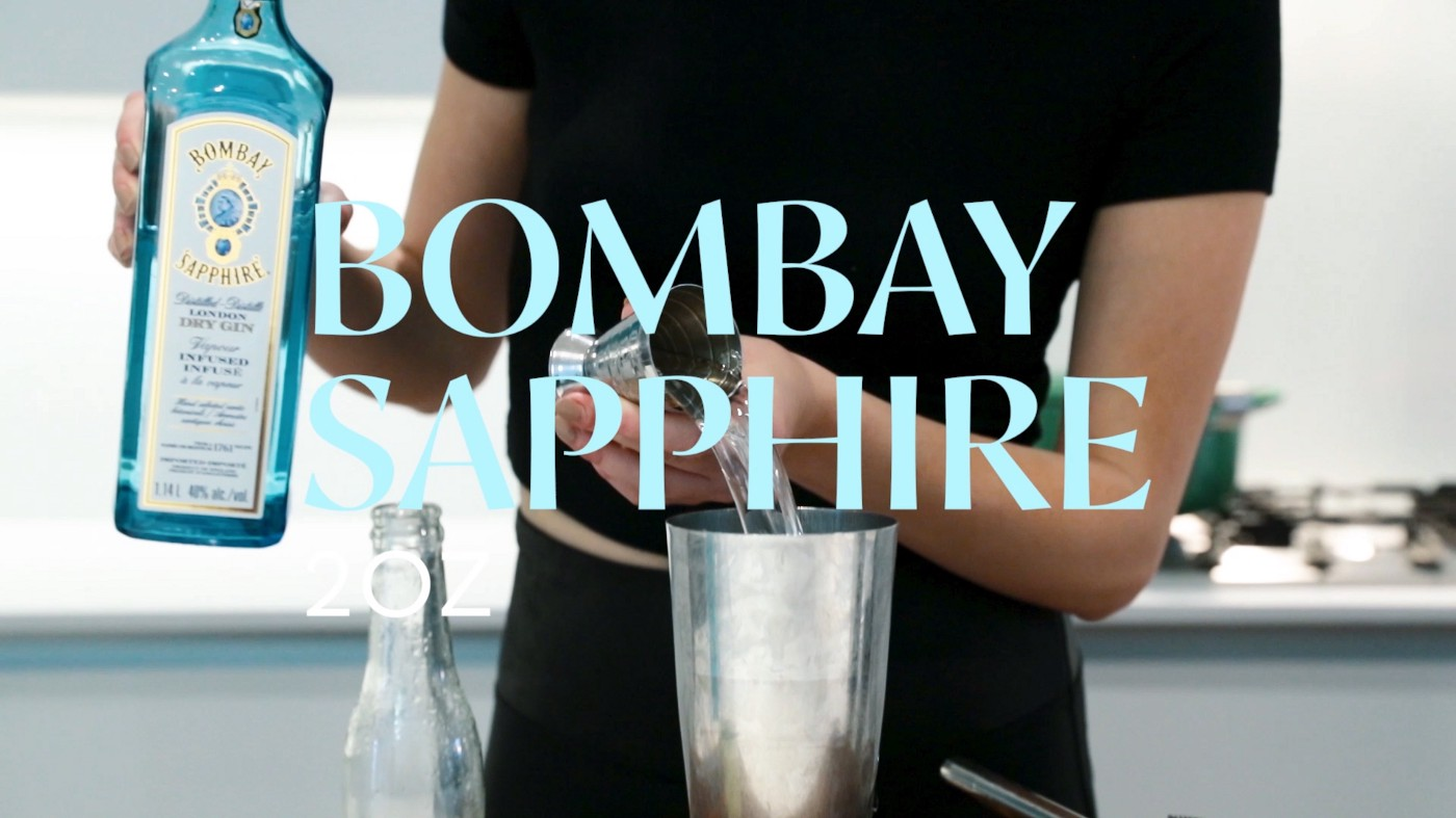 a model is pouring bombay saphire branded gin into a mixing cup