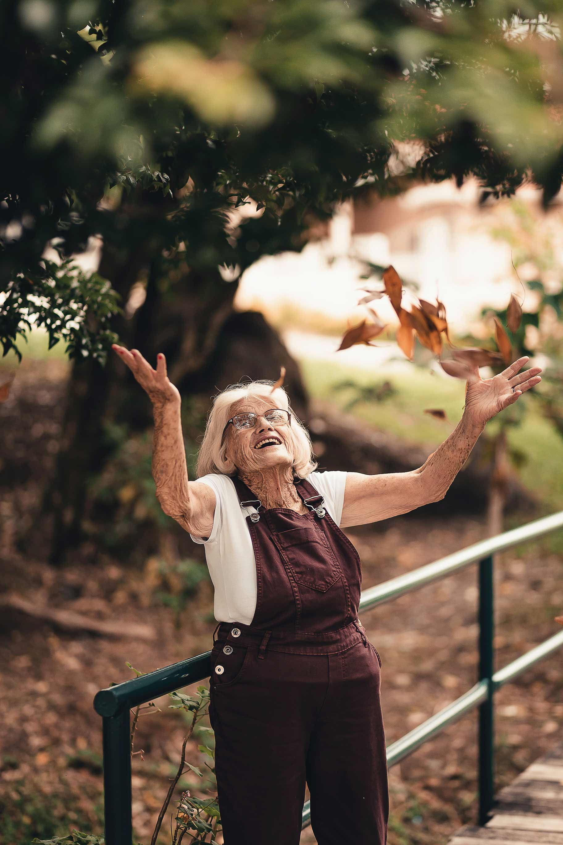 Elderly lady smiling and throwing leaves into the air
