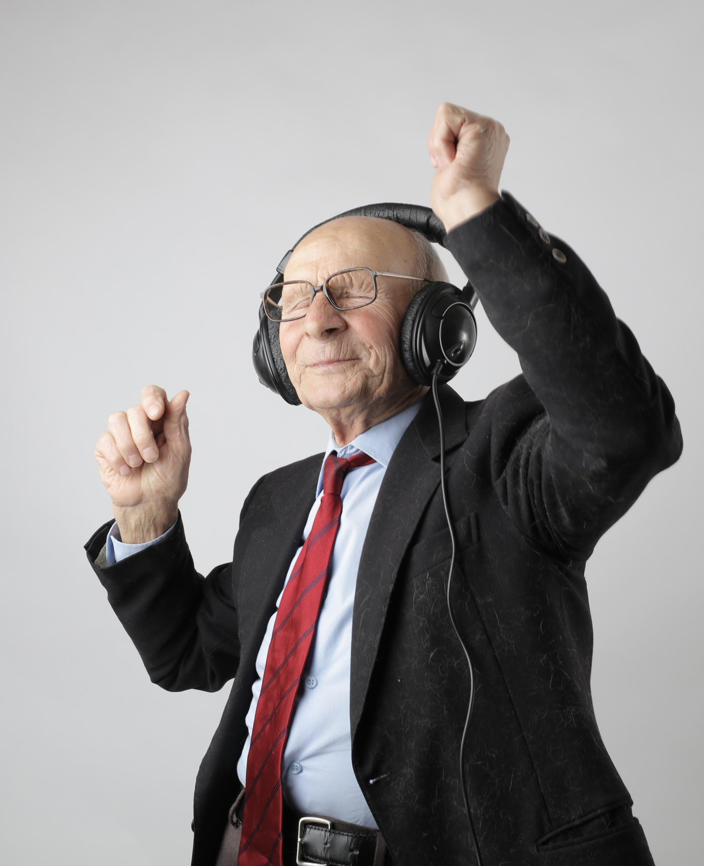 Elderly gentleman in a suit with headphones on and dancing