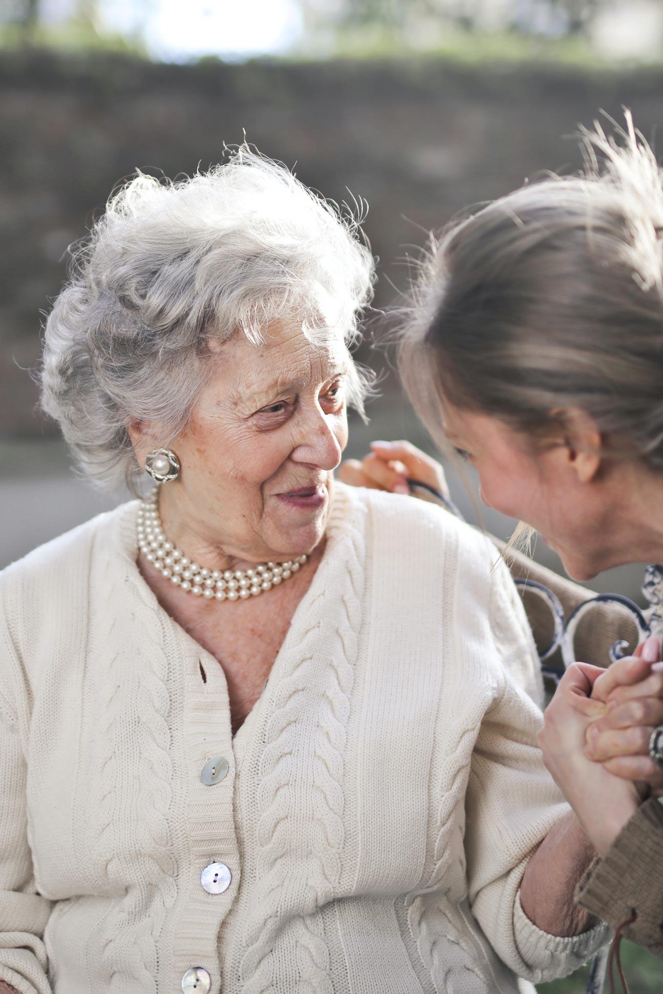 Elderly lady smiling at her female carer