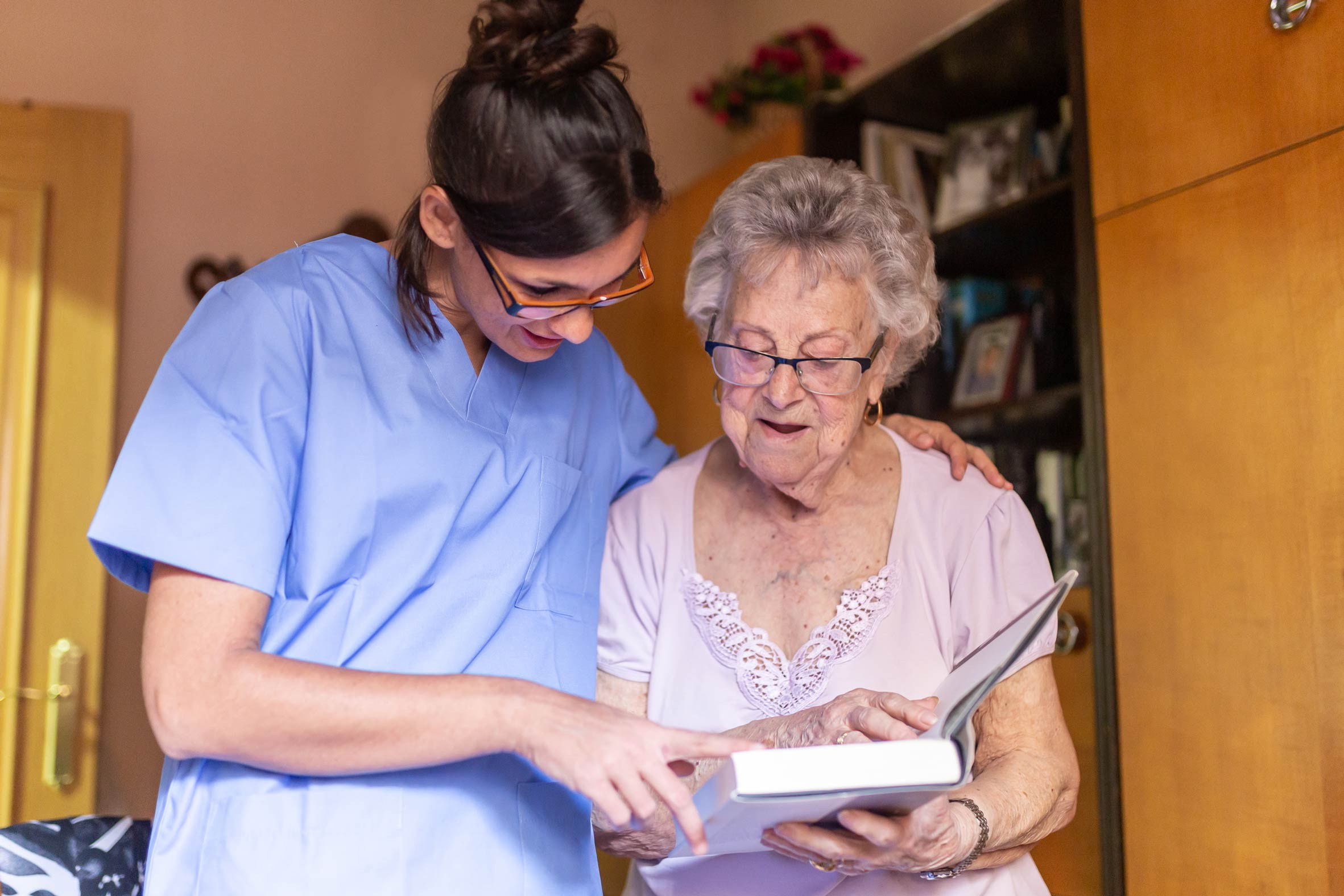 Elderly lady reading a book with a carer